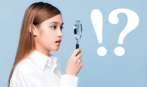 Young woman looking through a magnifying glass.