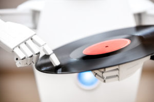 music robot is playing a record while touching with his finger the record. Cocept music streaming or downloading, futuristic music player