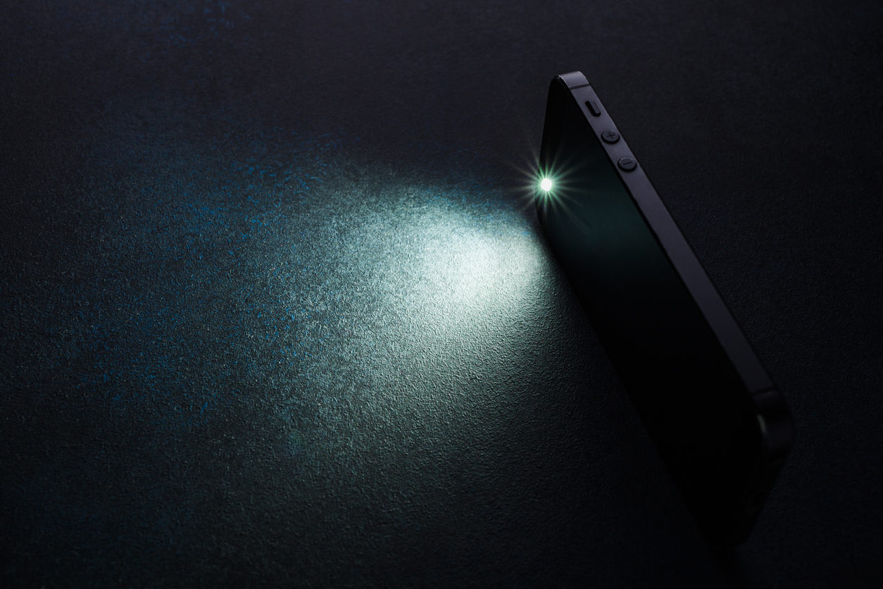 Lantern smartphone shines on a dark background.