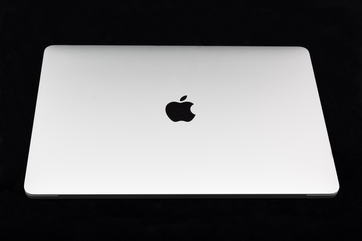 MacBook Pro Retina Display with Touch bar and a Touch ID sensor integrated into the Power button, made by Apple Inc. on black background.