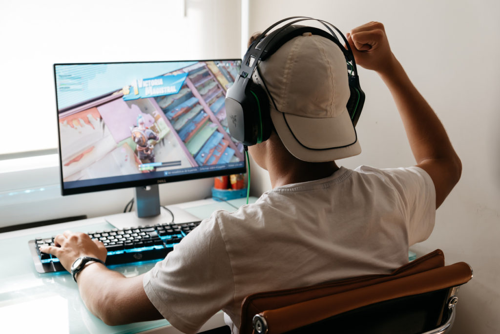 Teenager playing Fortnite video game on PC