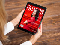 Woman reading fashion magazine on tablet