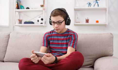 Excited teenage boy playing mobile game at home
