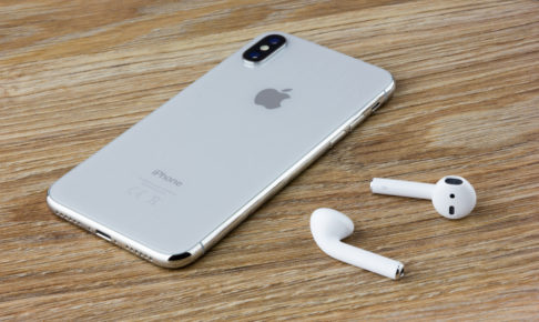 The Iphone 10 lies on a wooden table next to the wireless headphones airpods from the Apple.