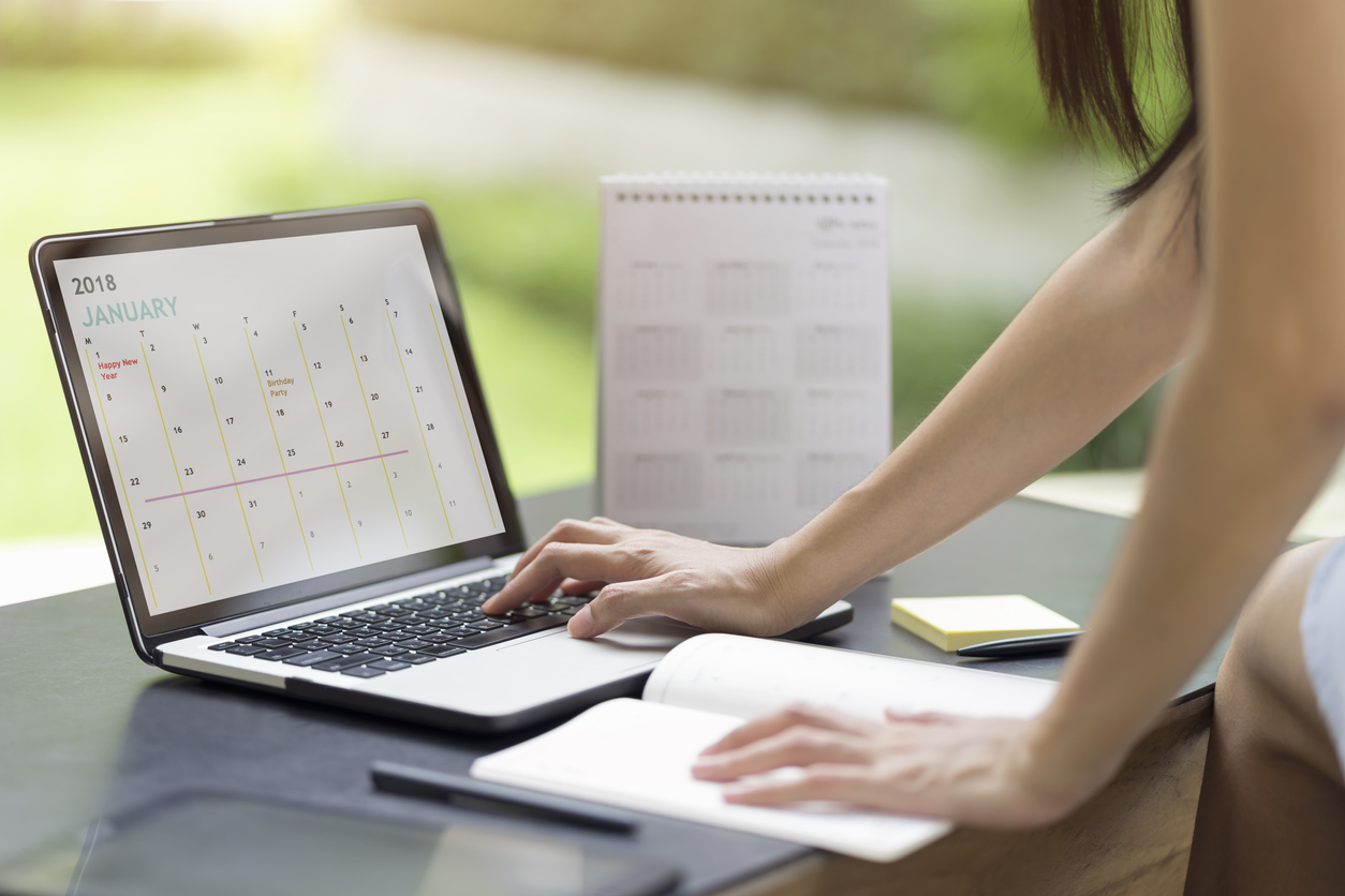 Woman planning agenda and schedule using calendar event planner. Woman hands using plan to vacation on computer laptop. Calender planner organization management remind concept.