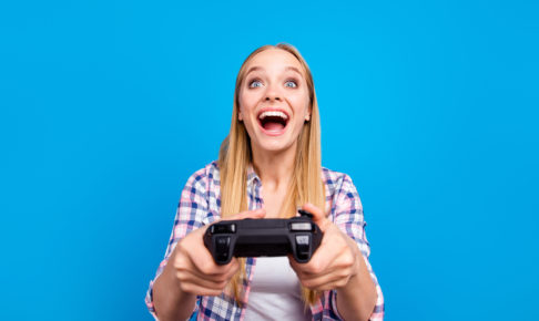 Close up of happy young blond girl holding joystick in hands and play in video games isoletad on blue background. Concept of victory and loses, competition and match