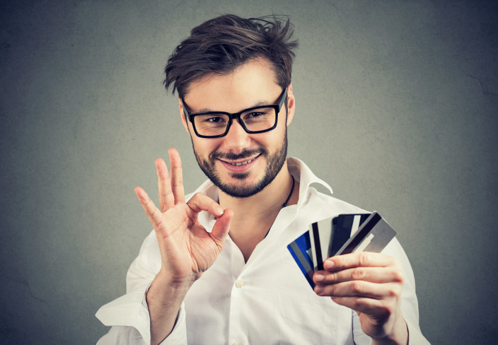 Content businessman in glasses holding pile of credit cards and showing OK gesture approving bank choice