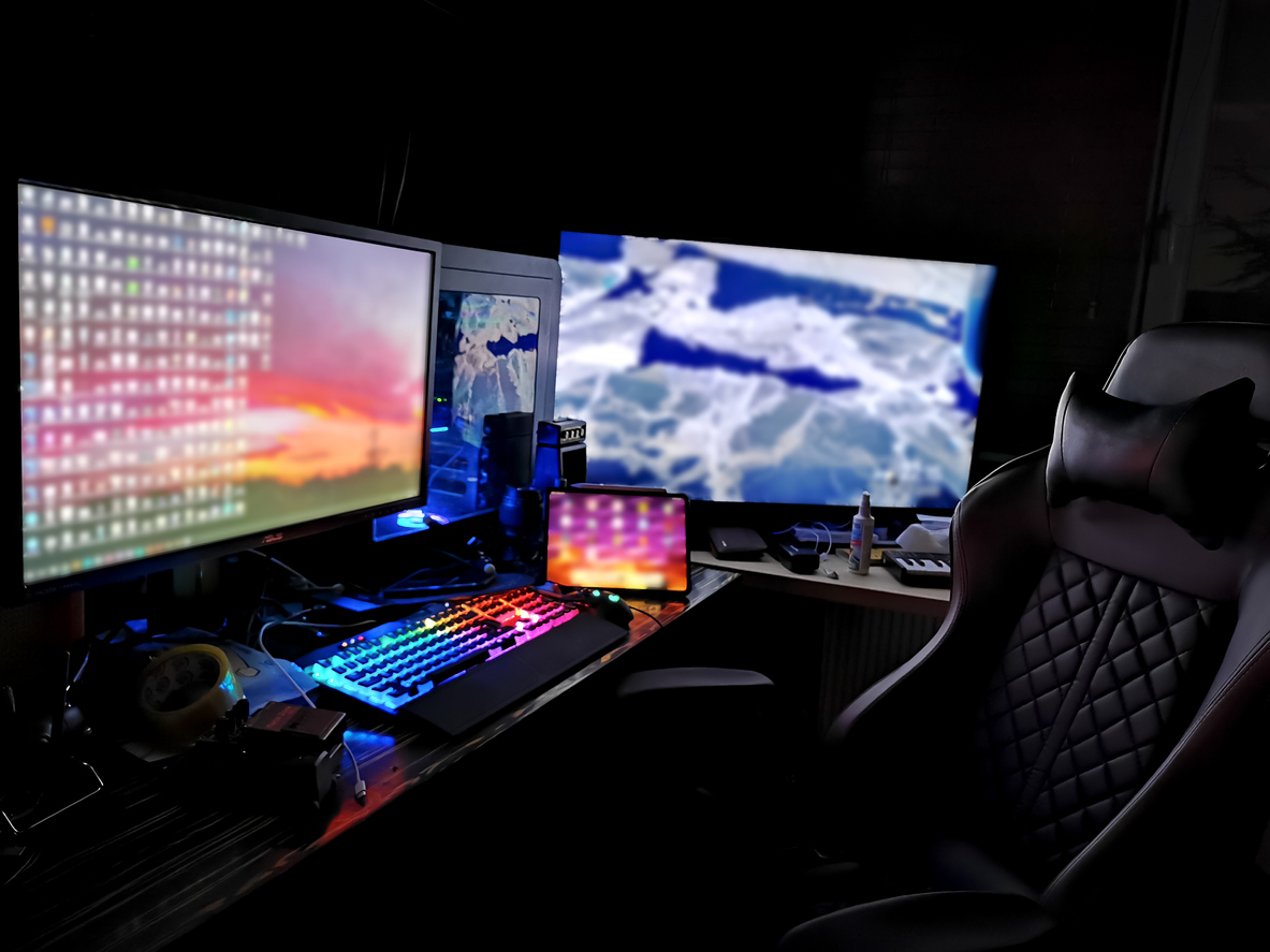 battle station gaming rig with multiple monitors for gamers coders miners designers renderers in a dark room with rgb lights on