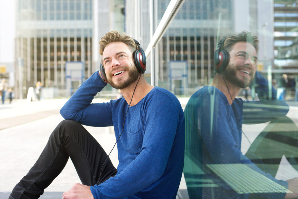 Portrait of a cool man smiling outside with headphones