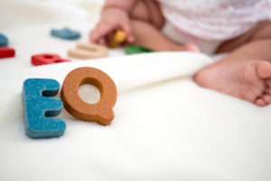 EQ text wooden word on blanket with blurred kid foot and copy space background,