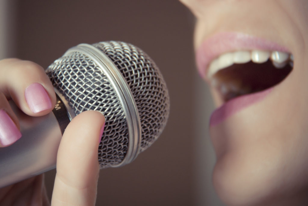 A woman sings into a microphone at a recording studio, her mouth close up