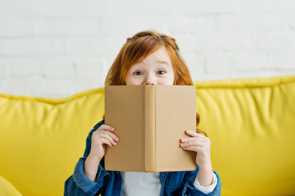 Child sitting on sofa and holding book in front of her face