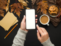 Woman holding cellphone with blank screen over autumn background