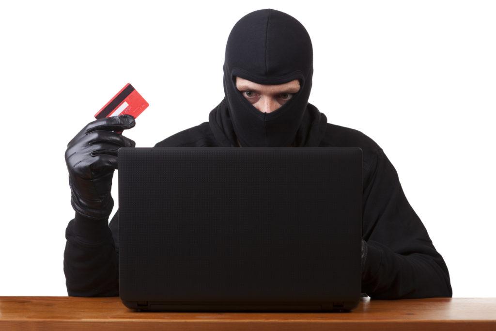 Masked man using stolen card to shop online. Internet theft concept.