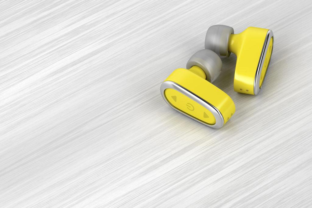 Yellow wireless in-ear headphones on wood table