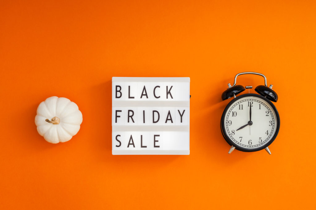 Creative Top view flat lay promotion composition Black friday sale text on lightbox alarm clock orange background copy space Template Black friday sale mockup fall thanksgiving promotion advertising
