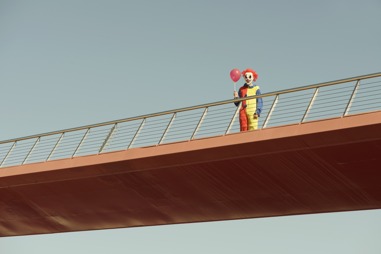 scary clown with a red balloon on a bridge