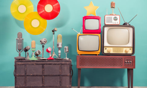 Retro studio microphones, outdated TV set, old FM radio, golden award star, flying multicolor LP vinyl record discs front blue background. Nostalgia music and journalism concept. Vintage style photo