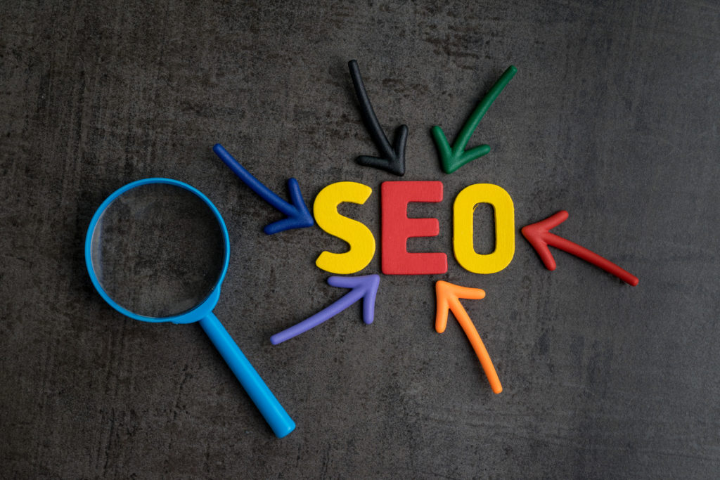 SEO, Search Engine Optimization ranking concept, magnifying glass with arrows pointing to alphabets abbreviation SEO at the center of cement wall chalkboard, the idea of promote traffic to website