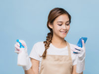 Young woman texting while cleaning.