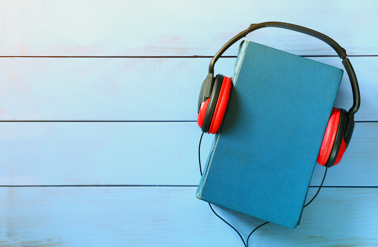blue cover book and headphones over wooden table