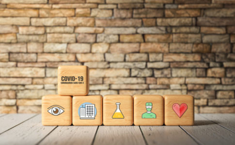 cubes with text COVID-19 and health icons in front of a brick wall - 3d rendered illustration