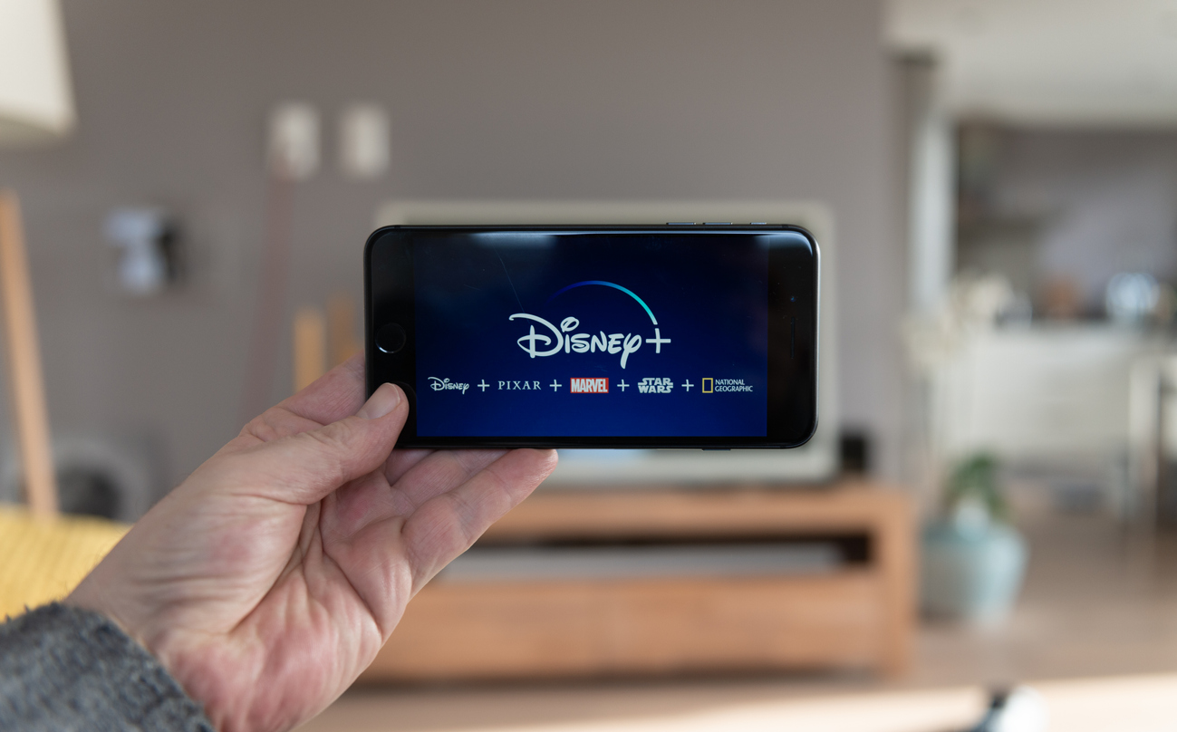 Disney+ startscreen on mobile phone. Disney+ online video, content streaming subscription service. Man holds his smartphone up and looks at disney plus
