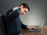 Businessman Suffering From Neck Pain Using Laptop At Desk