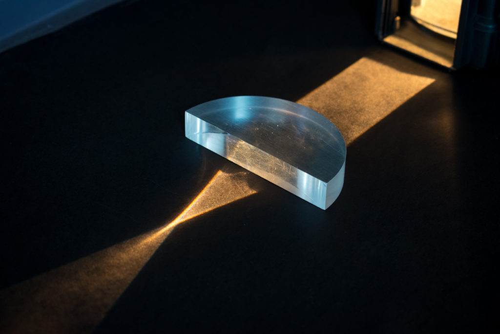 Passing of a lightbeam through a positive lens, showing a convergent pattern.