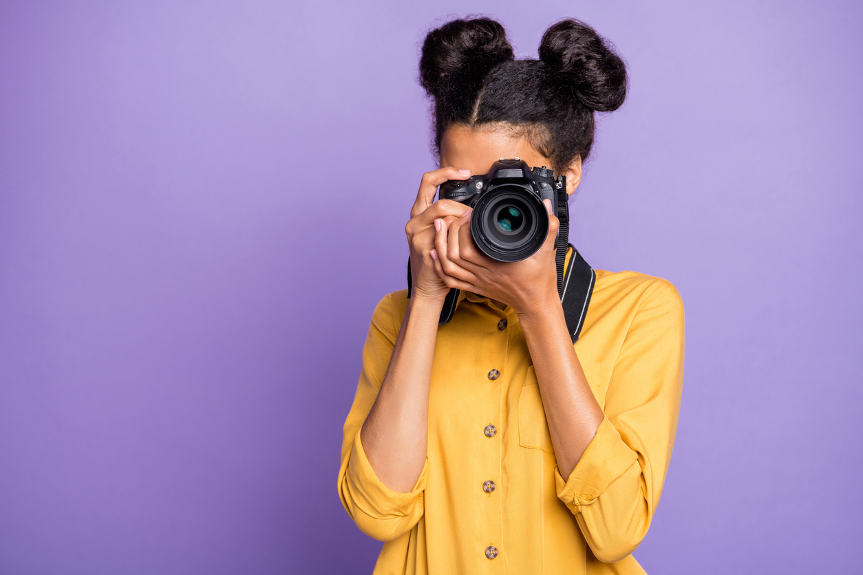 Photo of amazing dark skin lady holding photo digicam in hands photographing foreign sightseeing abroad wear yellow shirt trousers isolated purple color background