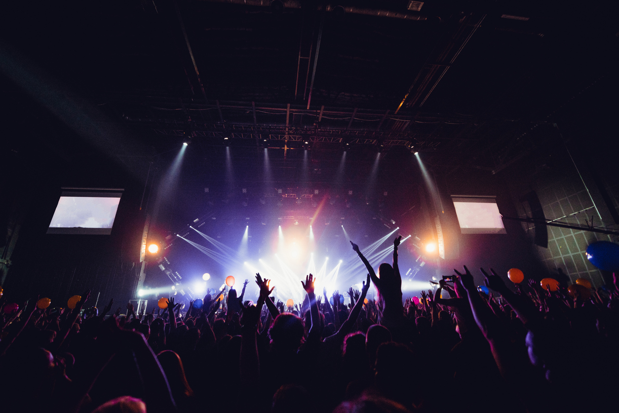 silhouettes of concert crowd in front of bright stage lights. Unrecognized people in crowd. Copy space background. Crowd of fans at music festive. Party in nightclub. Sold out concert.