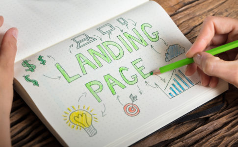 Human Hand Drawing Landing Page Concept On Notebook