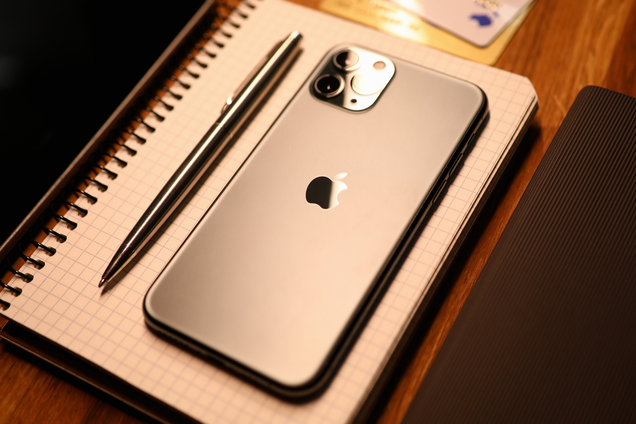 Apple iphone pro with silver pen on notebook