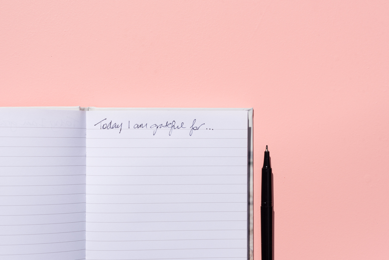 Gratitude journal and pen on pink background from above
