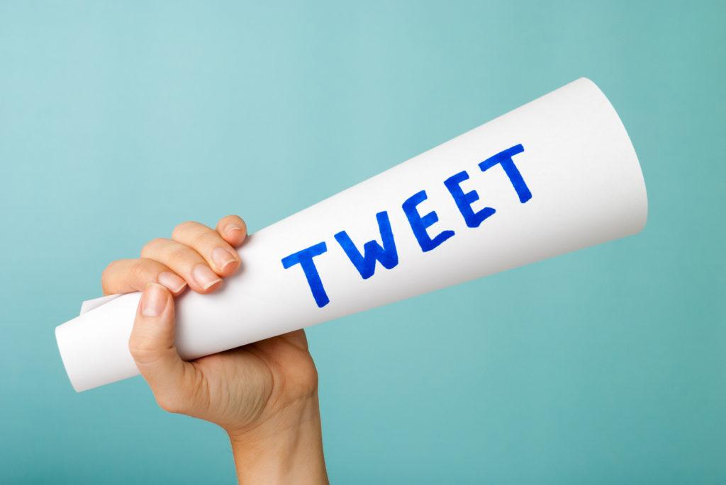 Hand showing blue tweet word handwritten, megaphone. Social media concept.