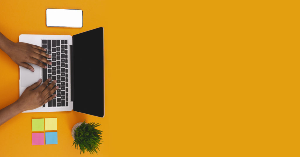 Afro woman typing on laptop at worplace with blank smartphone, plant and sticky notes on orange background, panorama with copy space