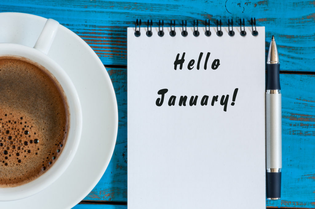 Hello January written on paper near morning coffee cup workplace. New year time concept. Business and office background. Top view.