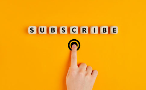 Male hand pressing subscription button with the word subscribe written on wooden blocks. Concept of online registration.