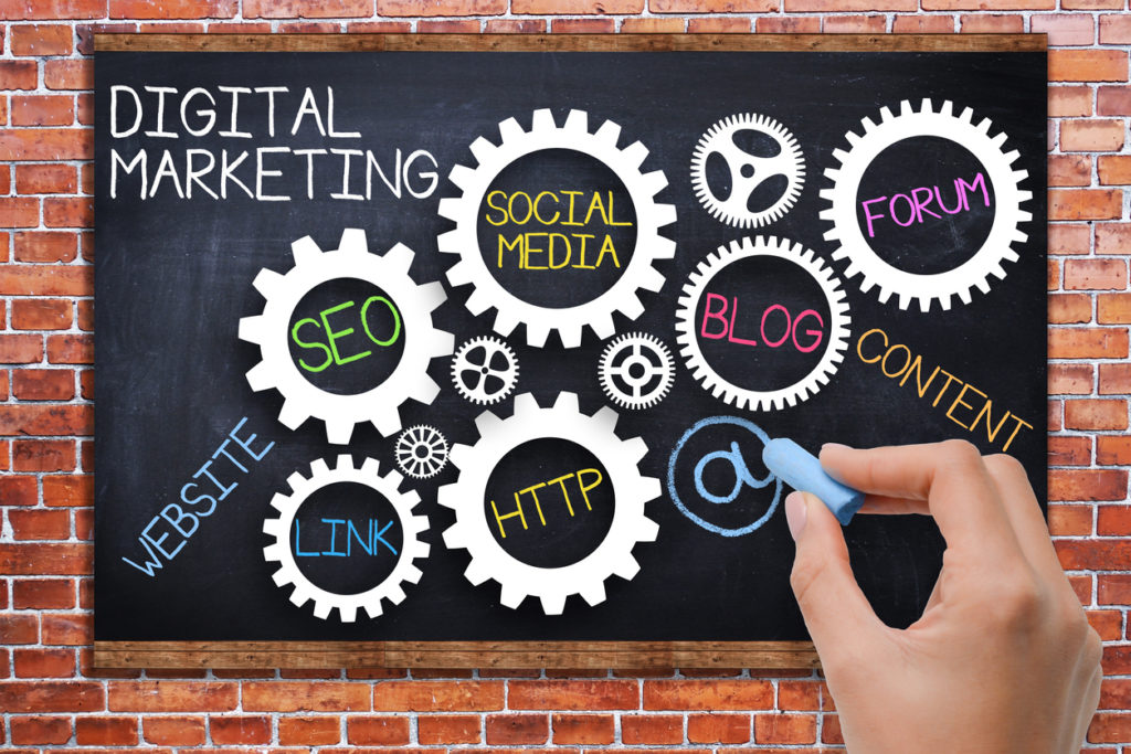 Digital marketing concept with spinning gears on blackboard