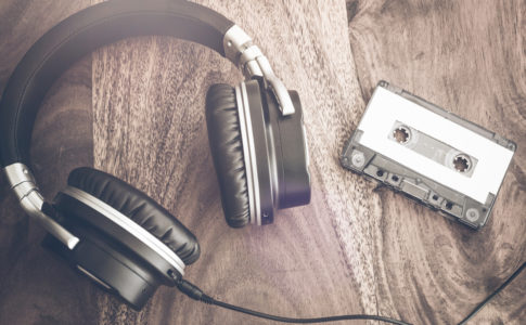 stereo headphones and audio cassette tape on rustic wooden table