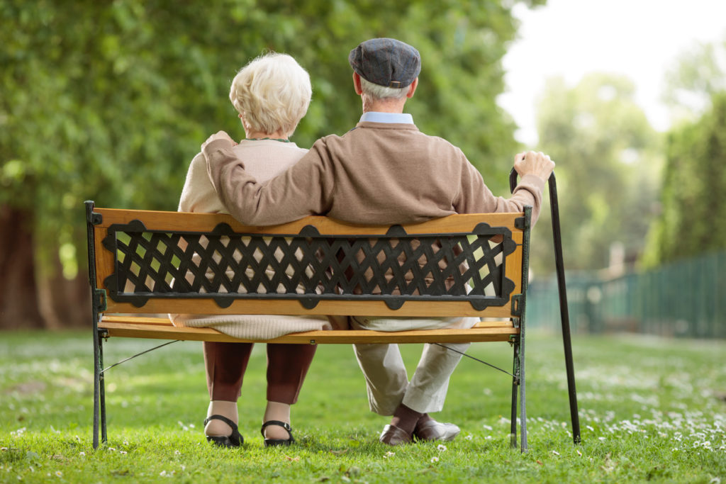 Senior couple sitting on a wooden bench in the park