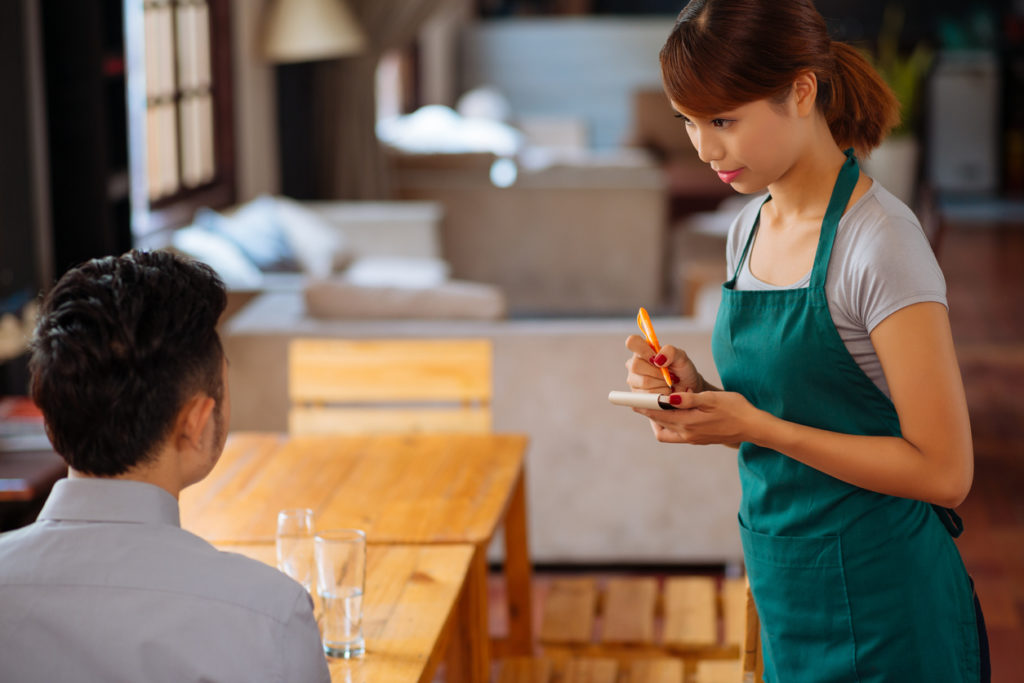 Pretty young waitress wearing apron standing at cafe table with notepad and pen in hands and taking order from male guest, blurred background
