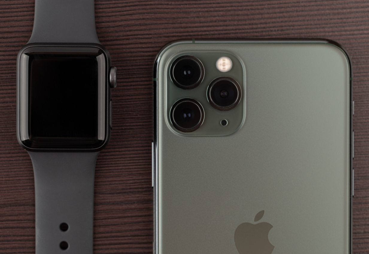 Apple iPhone 11 Pro Midnight Green on a wooden surface.