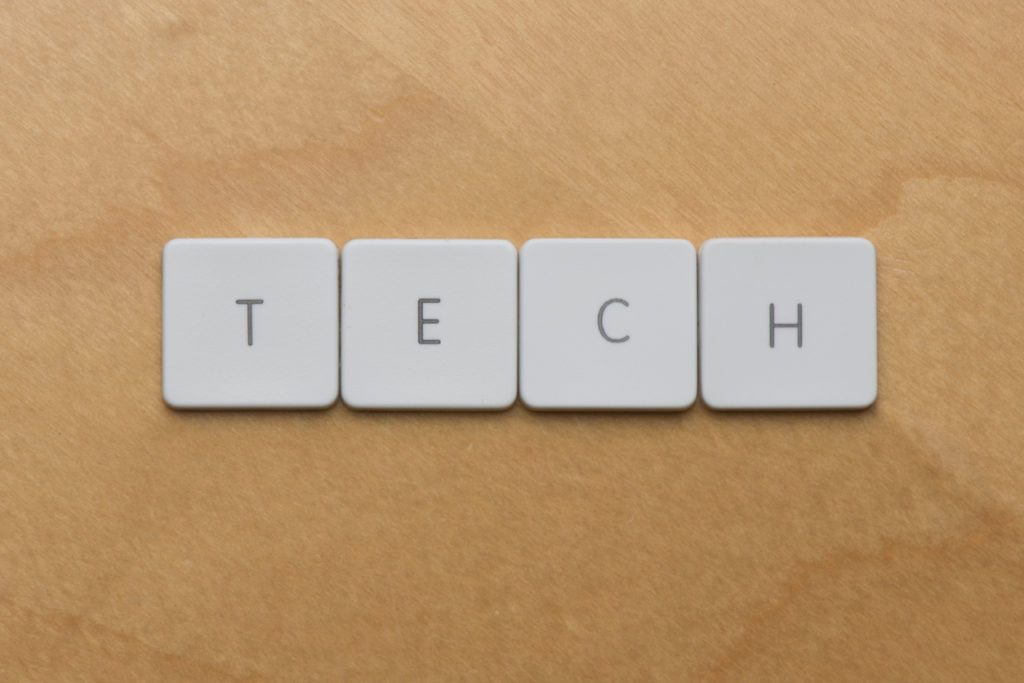 Keyboard letters spell the shorthand word tech on a desk background
