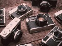 Retro film cameras on wooden background.