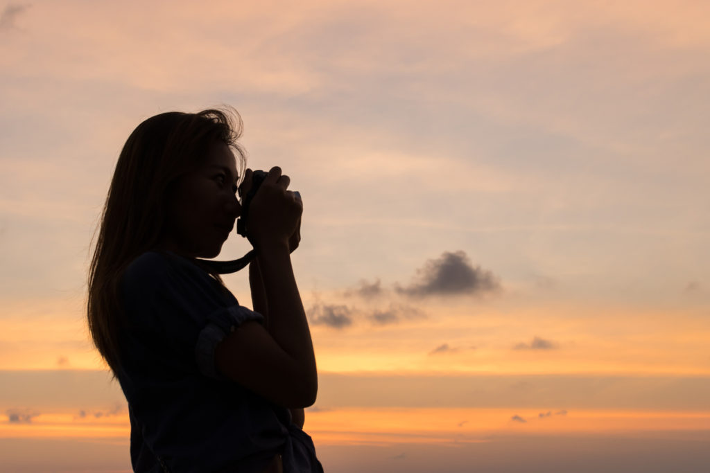 woman taking sunset photo by her camera on the beach.