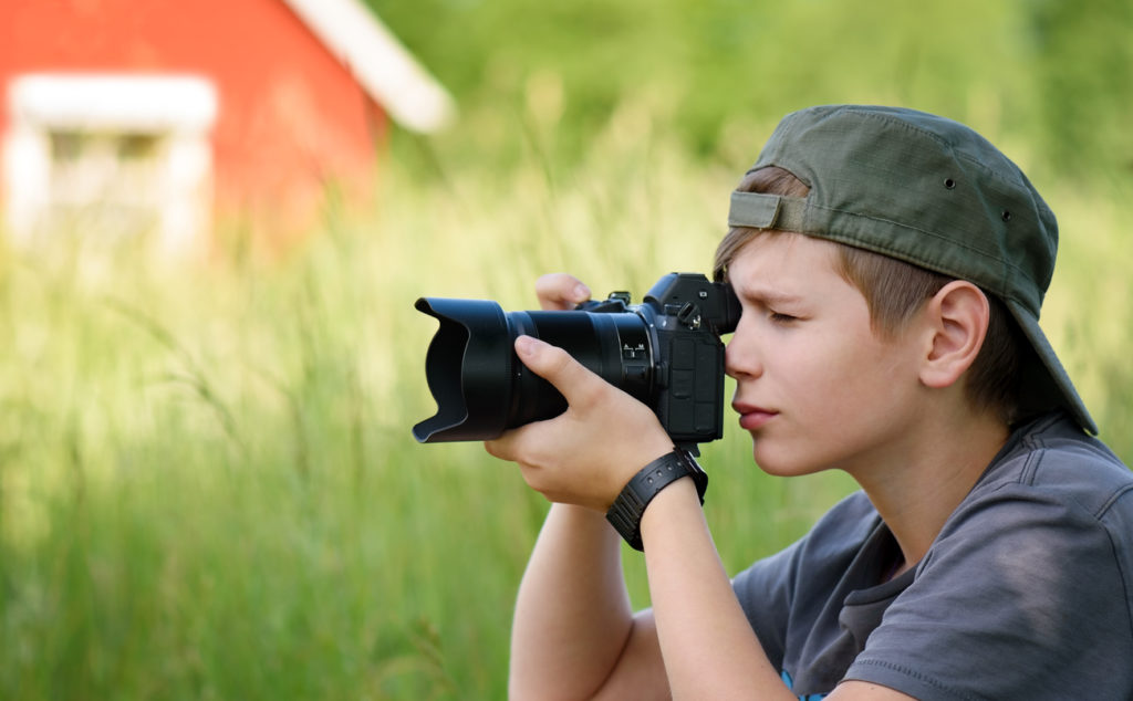 Boy with SLR camera shooting nature landscape in summer day in the village.