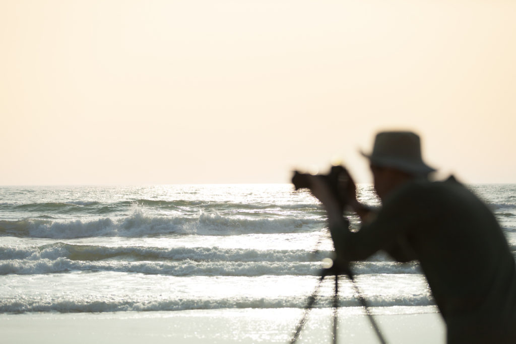 silhouette photographer at the beach, focus on waves.